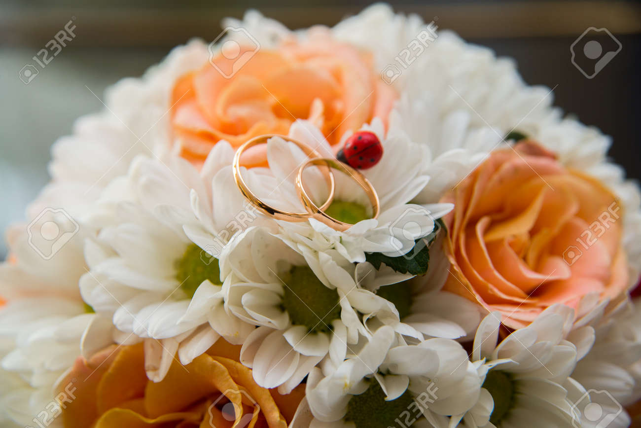 Two beautiful wedding rings lie on a wedding bouquet of orange roses stok fotoraf two beautiful wedding rings lie on a wedding bouquet of orange roses and white colors ladybug mightylinksfo