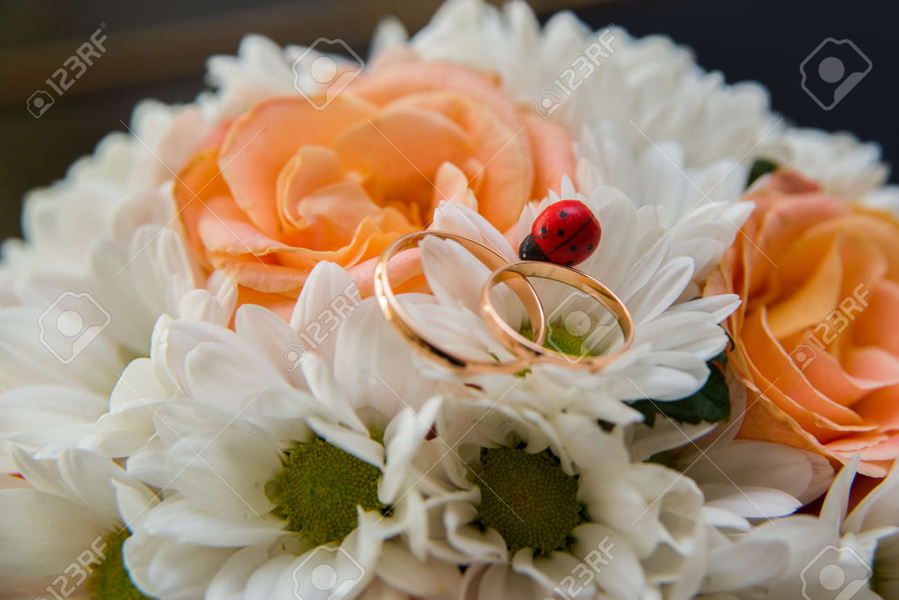 Two Beautiful Wedding Rings Lie On A Wedding Bouquet Of Orange