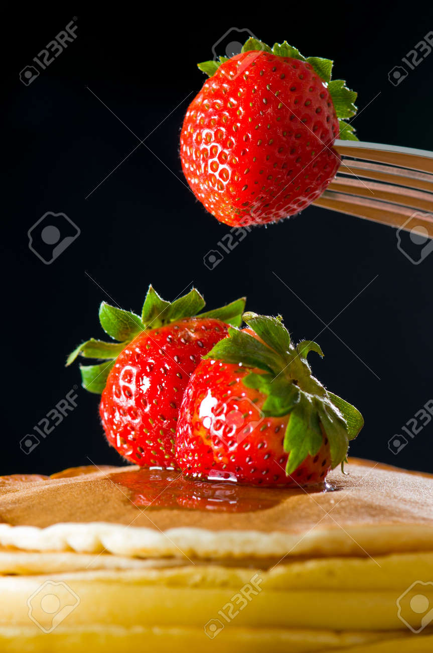 Strawberry butter pancake with honey/ maple sirup flowing down closeup shoot, one strawberry lifting up Stock Photo - 7716637