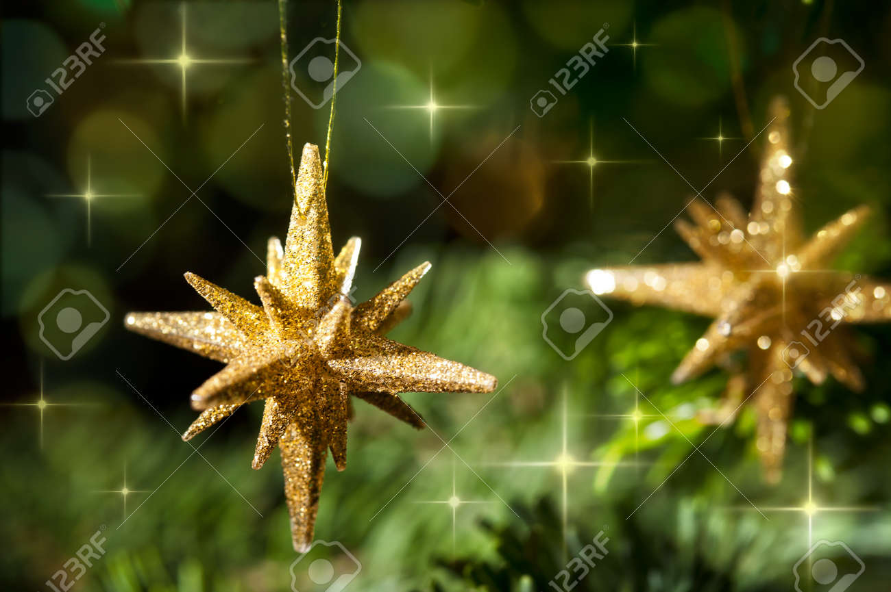 Decorative Gold Star Ornament In A Christmas Tree Infront Of A Glitter  Background Stock Photo