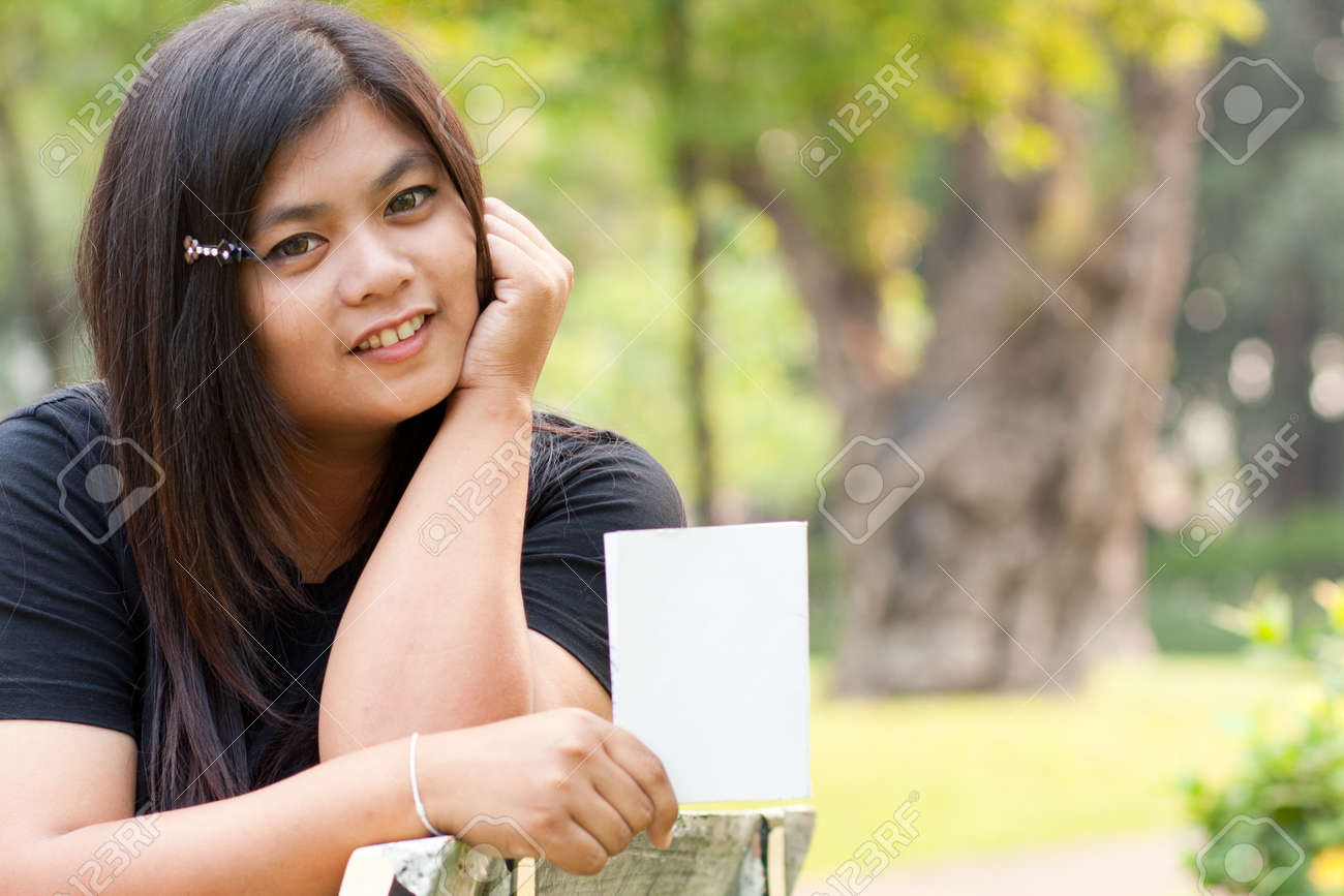 Women sitting in the park and hold a white card. Stock Photo - 8893752