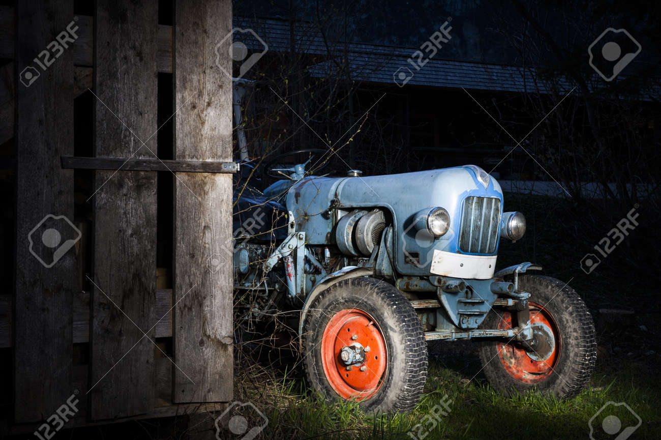 blue oldtimer farming tractor standing next to a wooden hut at night with red painted tires Stock Photo - 13980317