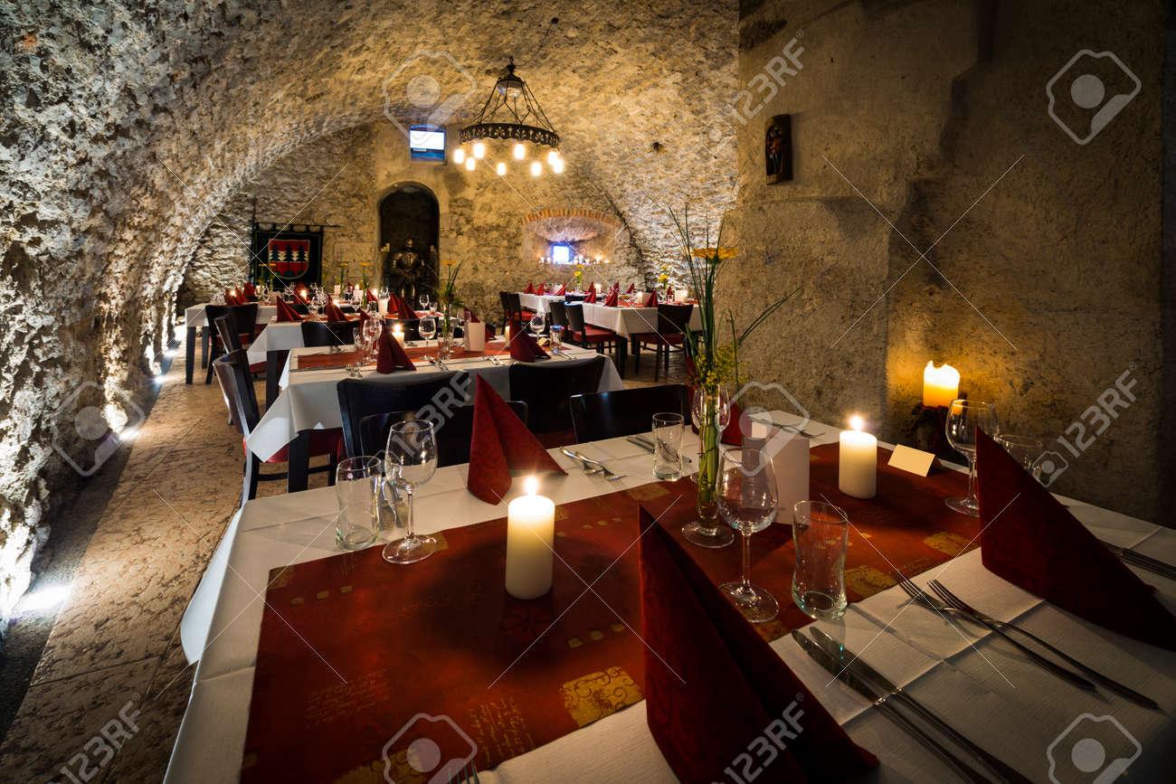 Romantico arco di muro di pietra in camera cavaliere con tavoli e ...