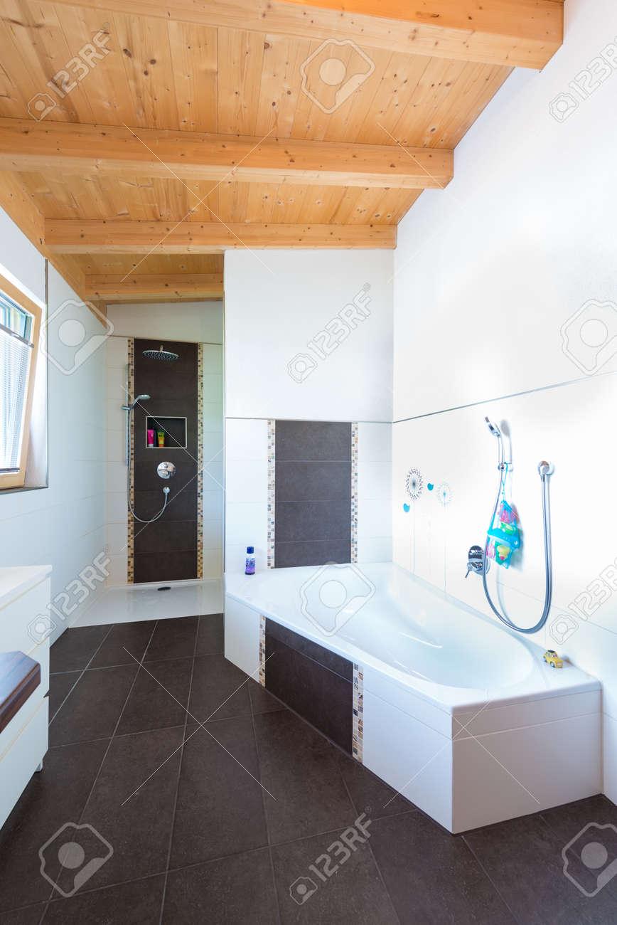 bad mit badewanne in holzhaus und dunkelbraun fliesenboden, Moderne