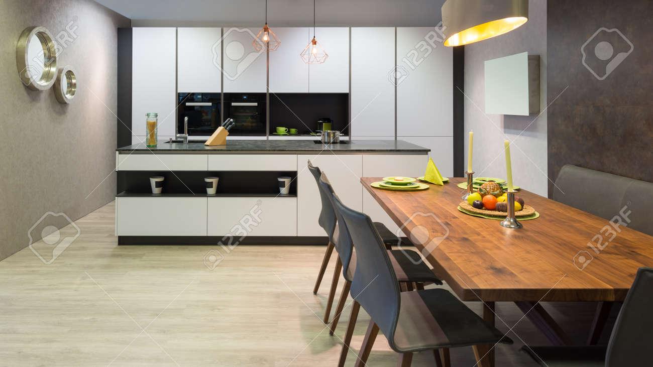 Cucina bianca piatta con unità di isola e tavolo da pranzo in legno