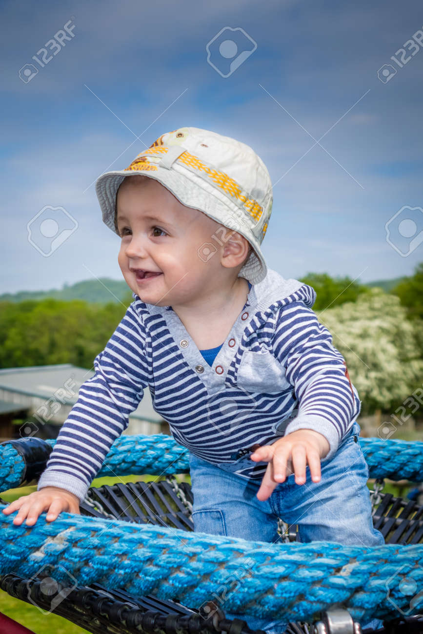 Cute Little Baby Boy Standing On A Small Carousel In The Park