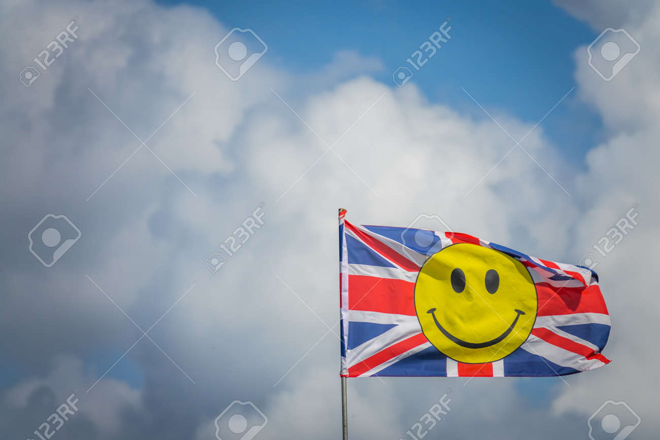 British Flag With Yellow Smiley Face Fluttering In A Strong Wind