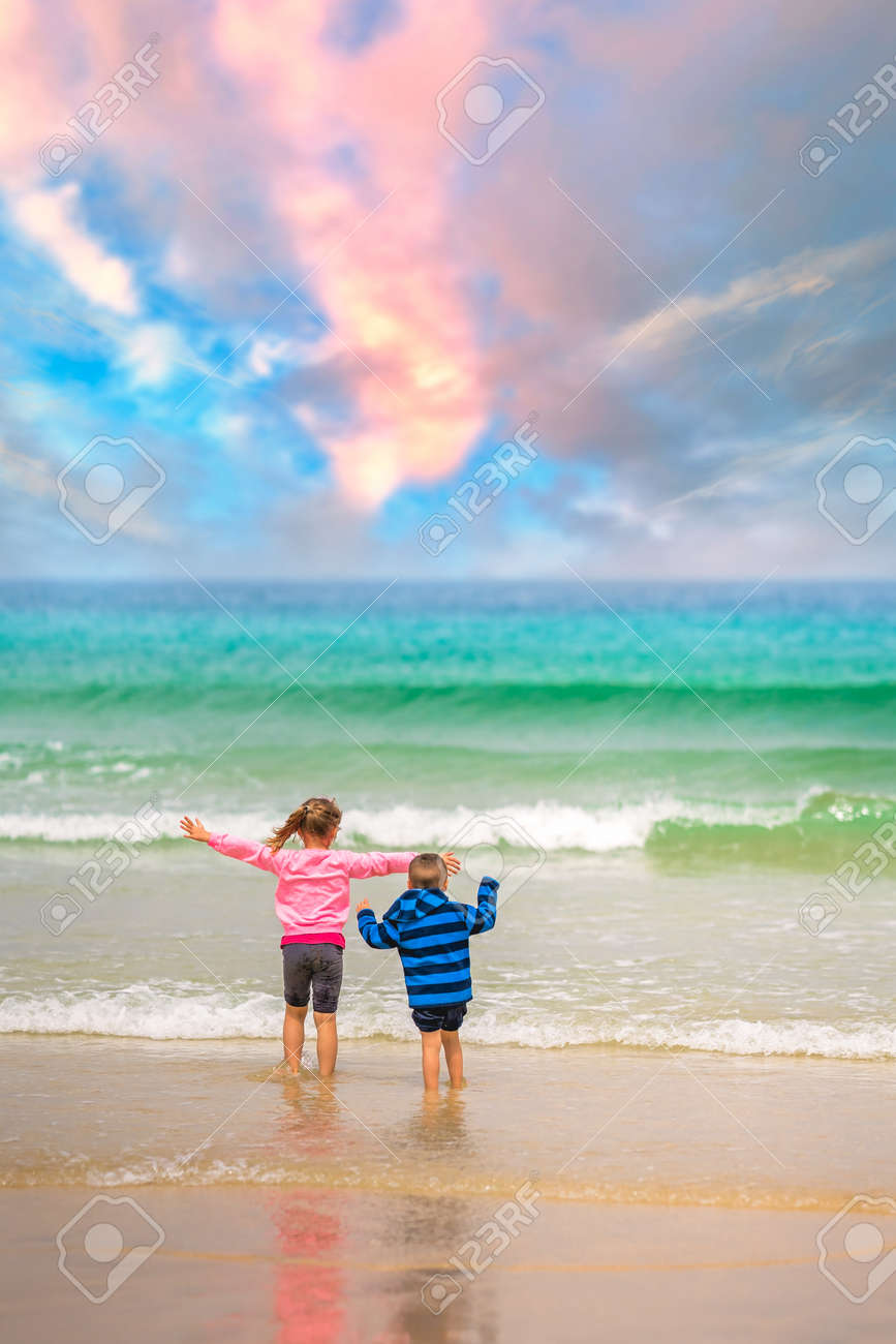 Little boy and girl standing on the sea shore beach and waiting for the incoming waves in summer - 126594484