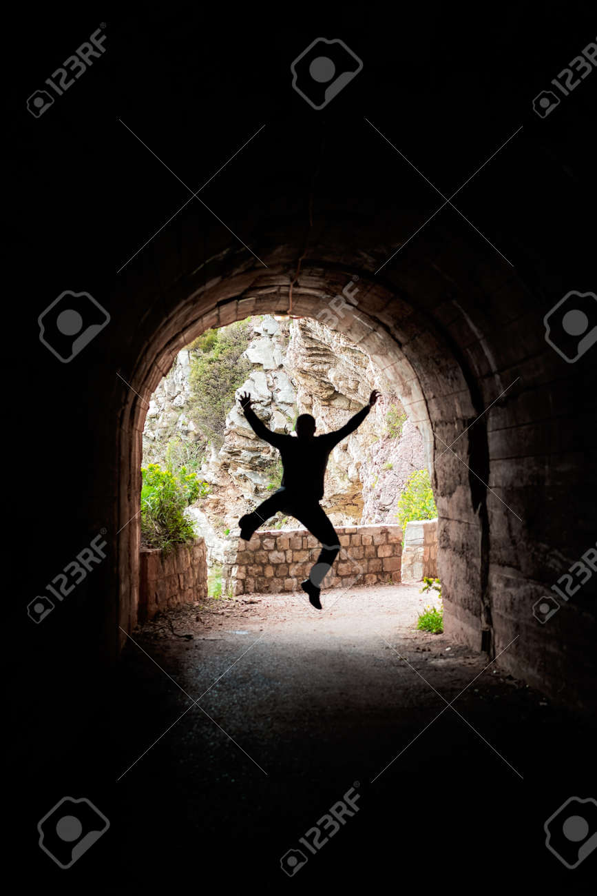 Silhouette of a man jumping in a dark tunnel on the walking path in Petrovac bay,Montenegro - 126594603