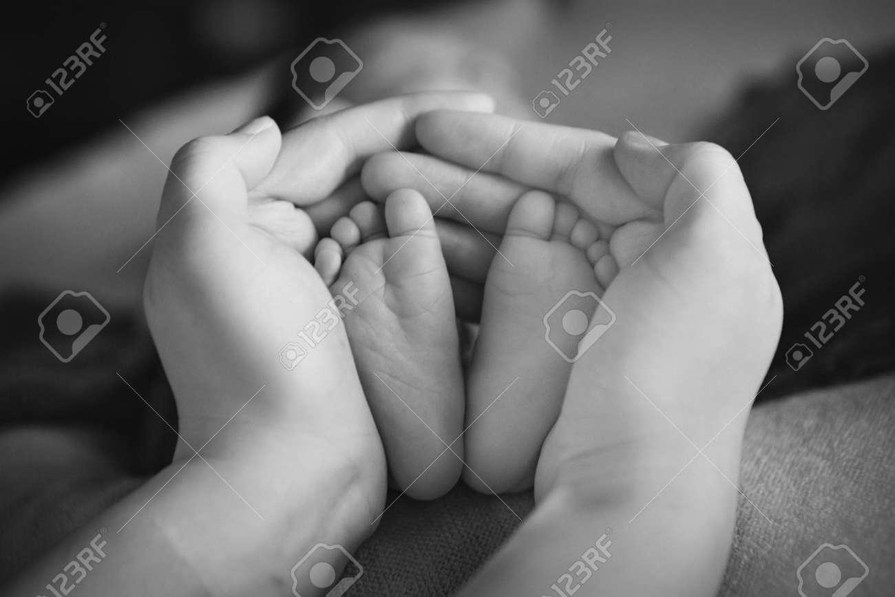 Newborn babys feet mother holding newborn baby legslegs massage stock photo 107843277