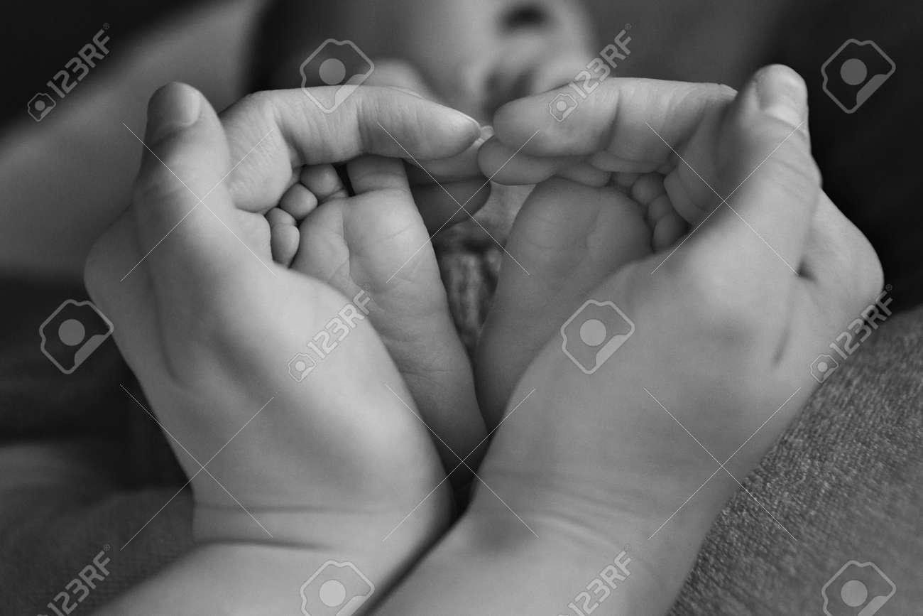 Newborn babys feet mother holding newborn baby legslegs massage stock photo 109363875