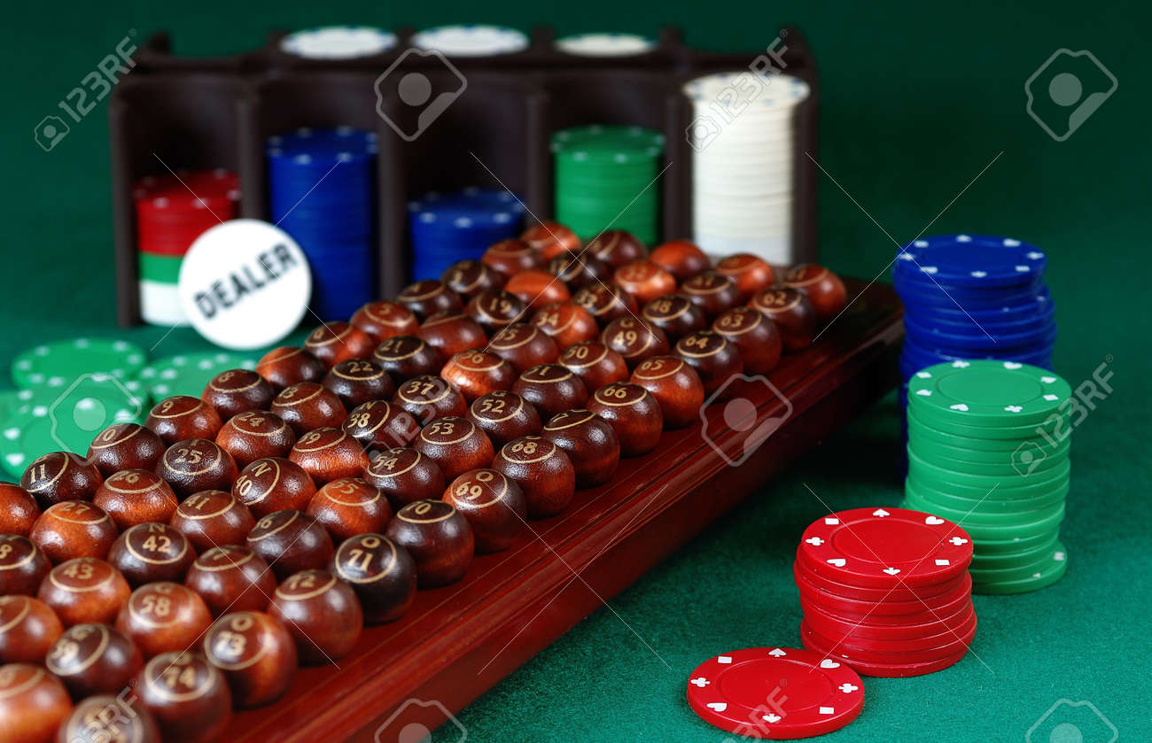 wooden bingo balls, stack of Poker chips and dealer button on a green background Focus on ball 54 Stock Photo - 12805336