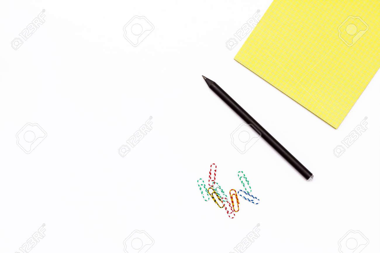 Crayon noir trombones colorés et un bloc notes jaune bureau de