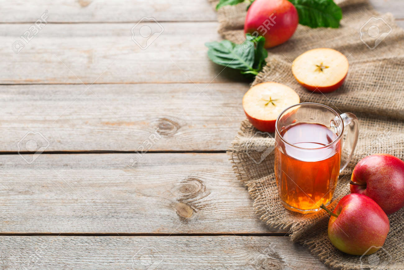 Food and drink, harvest autumn fall concept. Fresh organic apple juice in a mug with ripe fruits on rustic wooden background. Copy space - 129850378