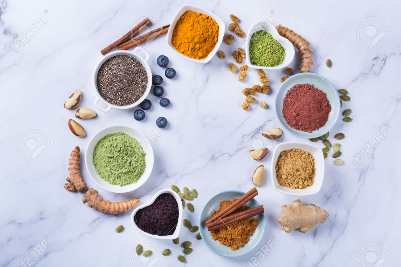 Balanced nutrition concept for clean eating antioxidant detox diet. Assortment of superfood powder - acai, turmeric, wheat, ginger, cinnamon, matcha. Flat lay marble background - 141204496