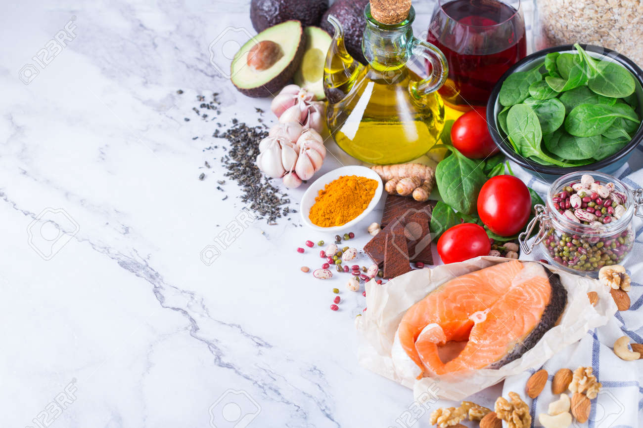 Balanced diet food concept. Assortment of healthy food low cholesterol, spinach avocado red wine green tea salmon tomato flax chia seeds turmeric garlic nuts olive oil - 163638007