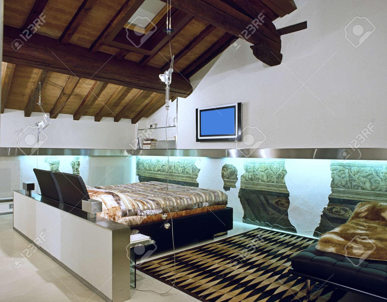 Moderne slaapkamer op de zolder ruimte met houten plafond en ...