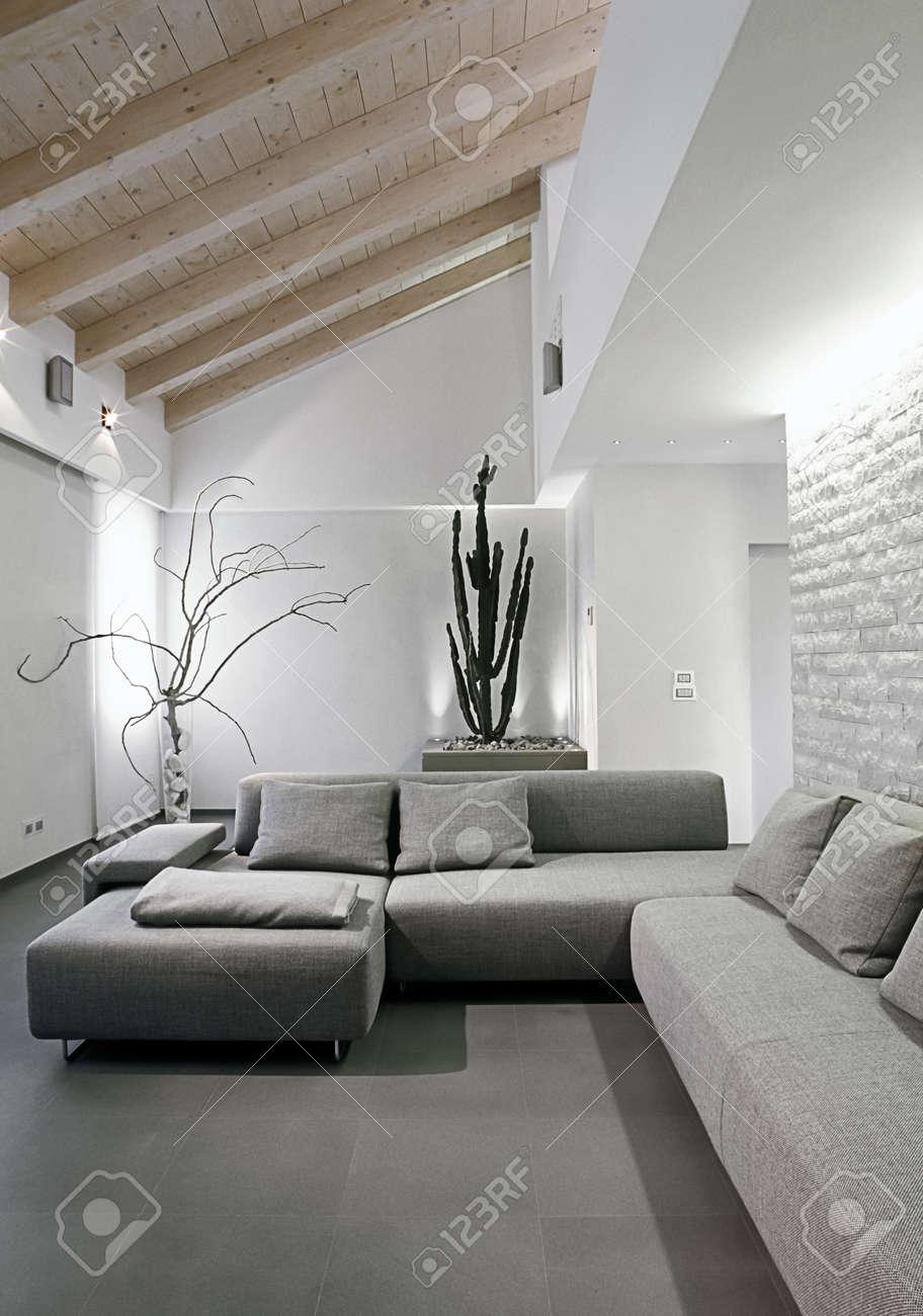 moderno divano grigio nel vivere in una mansarda moderna foto ... - Arredamento Moderno Mansarda