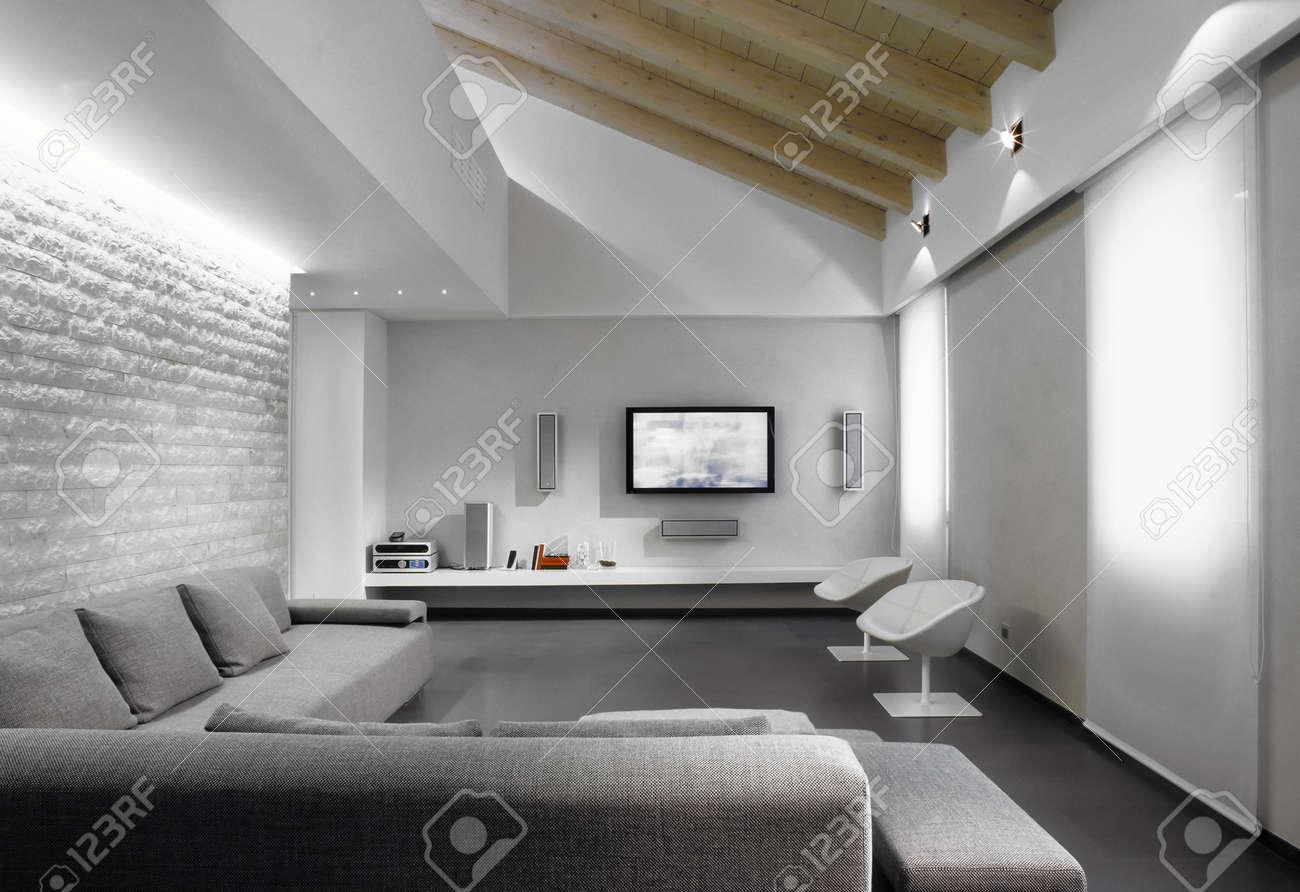 Moderne grijze sofa in de woonkamer in een moderne zolderkamer ...