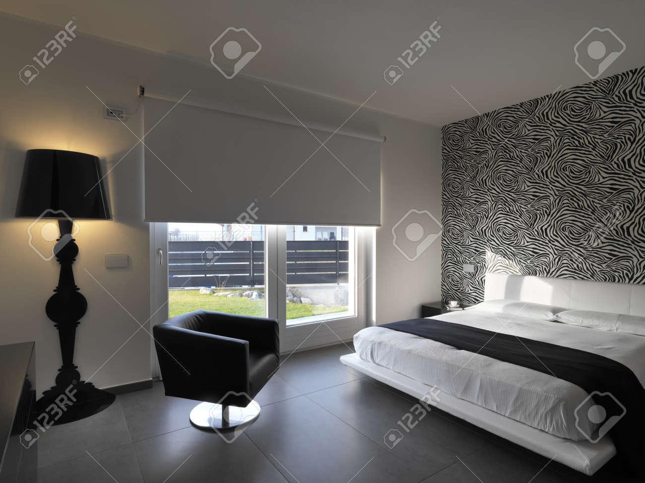 Moderna sovrum med skinnfåtölj och svart vägglampa royalty fria ...