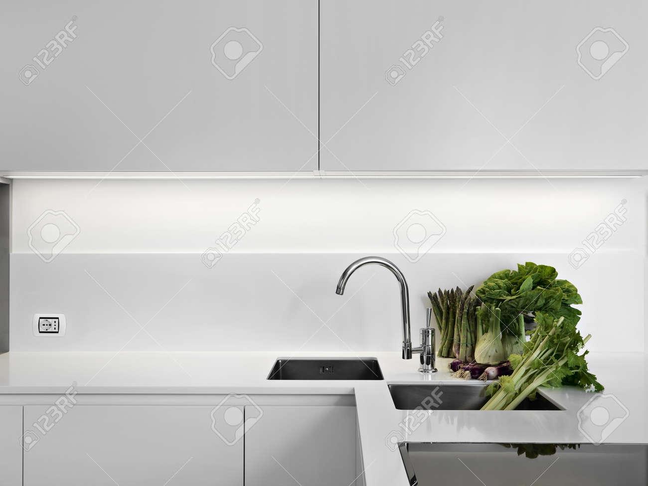 modern white laminate kitchen with vegetables on the white worktop Stock Photo - 15375078