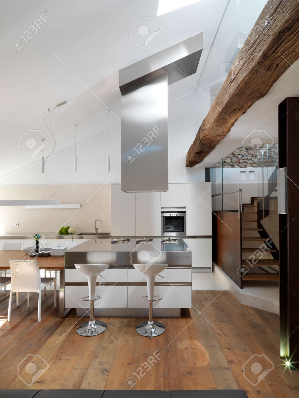 view of island modern kitchen with wood floor near to staircase in the penthouse Standard-Bild - 30110279
