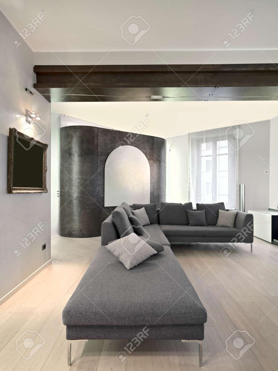 Canapé en tissu gris dans le salon moderne avec plancher de bois