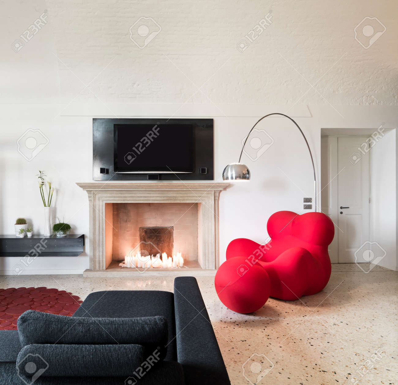 Black Sofa Red Armchair And Fireplace In A Modern Living Room