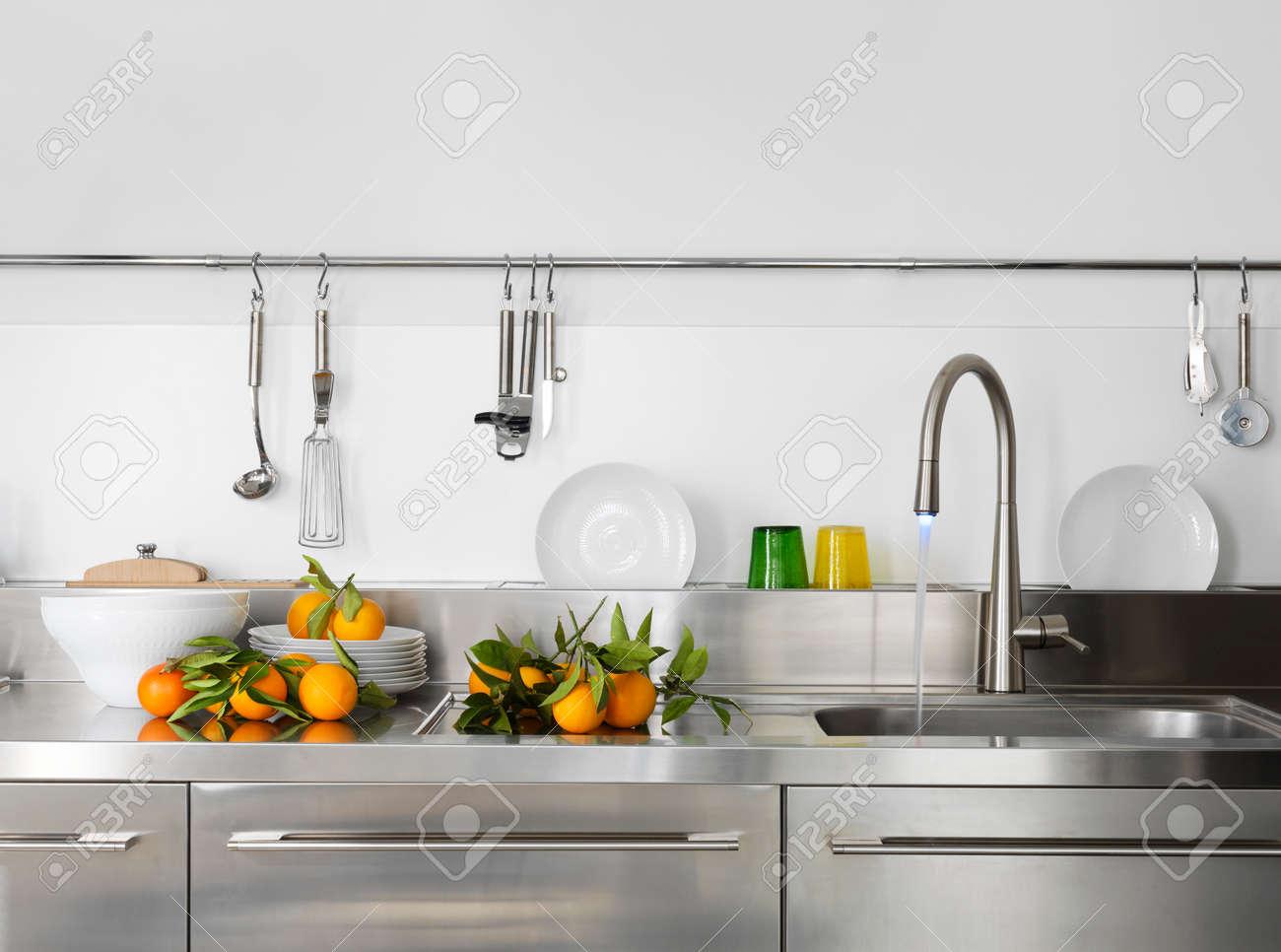 fresh orange on the worktop near to sink in a modern kitchen Standard-Bild - 30779315
