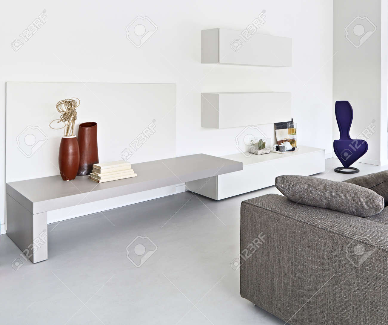 Vue de l\'intérieur d\'un salon moderne avec canapé en tissu et plancher de  béton