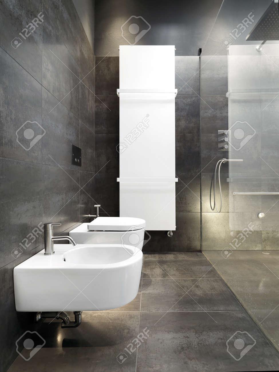 archivio fotografico dettaglio di sanitayware e riscaldamento in un bagno moderno con piastrelle scure