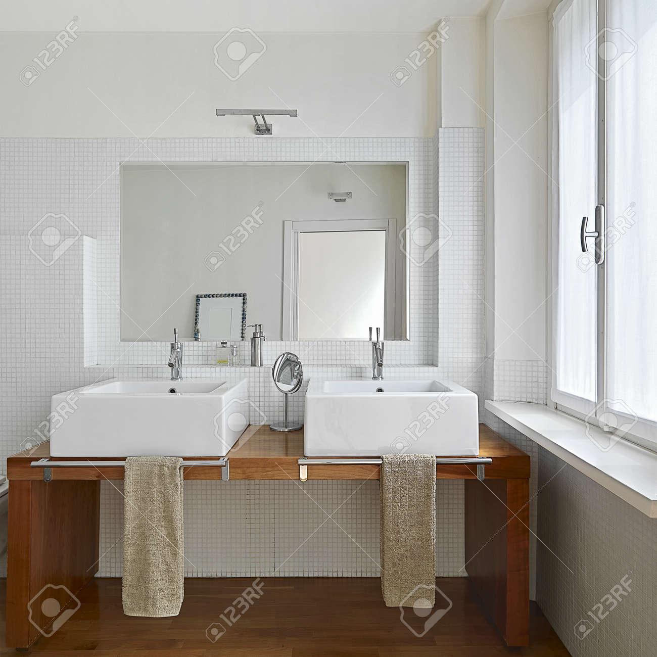 archivio fotografico vista interna del bagno moderno con due lavabo e pavimento in legno