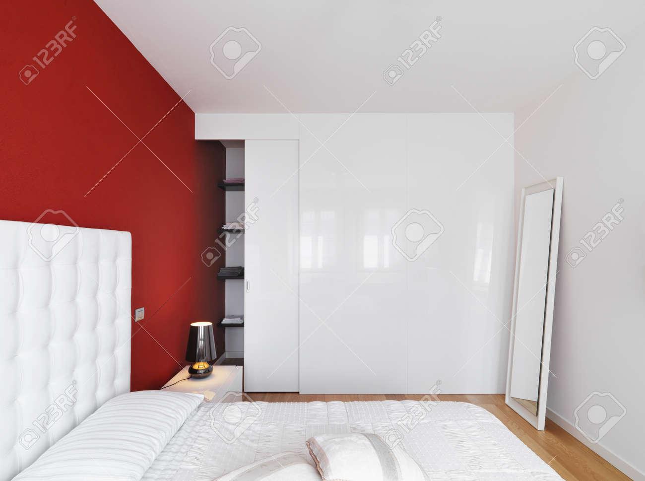 Luxe moderne slaapkamer met een rode muur en houten vloer royalty ...