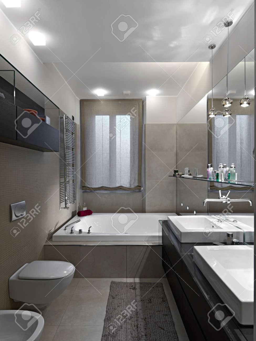 Vue intérieure de salle de bains moderne avec baignoire sous la fenêtre et  foregorund de sanitaruware