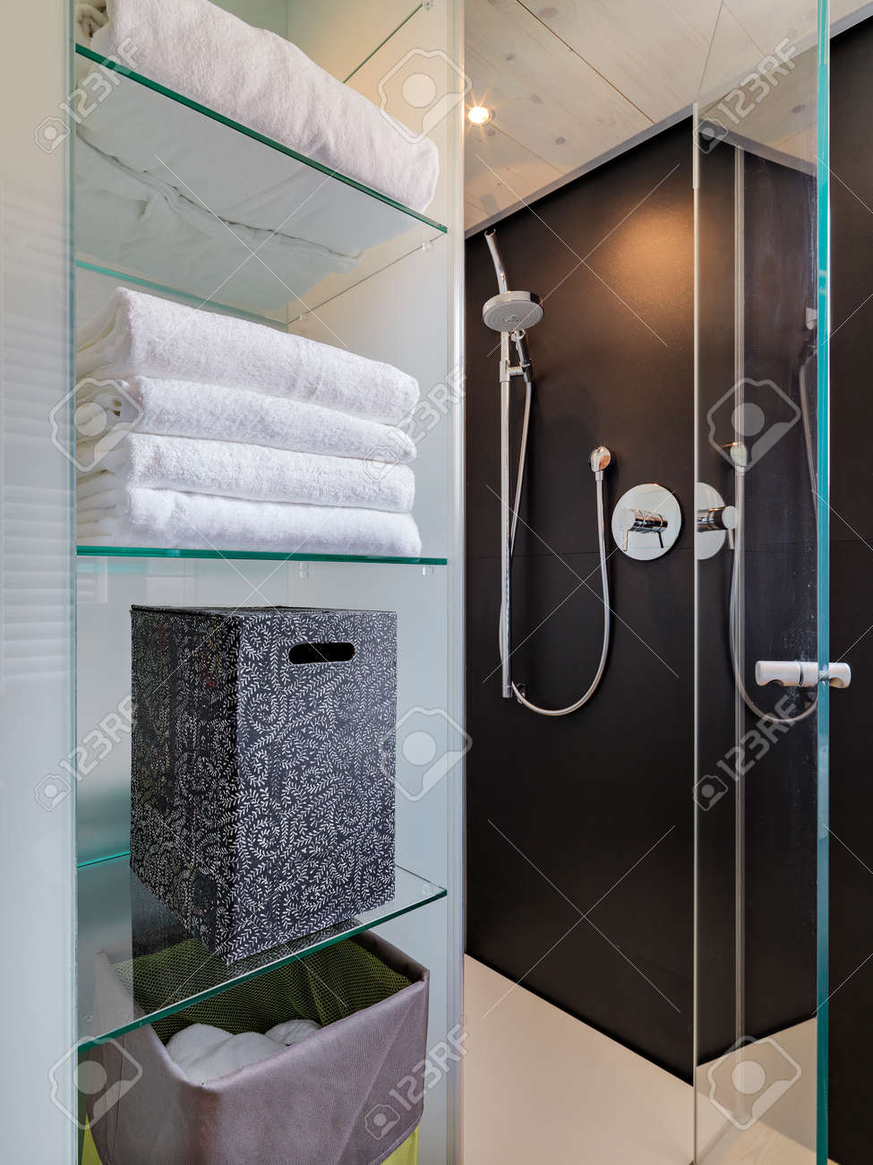 Glass box bathroom - White Towel And Box On The Glass Shelves Overlooking On Glass Shower Cubicle In The Modern