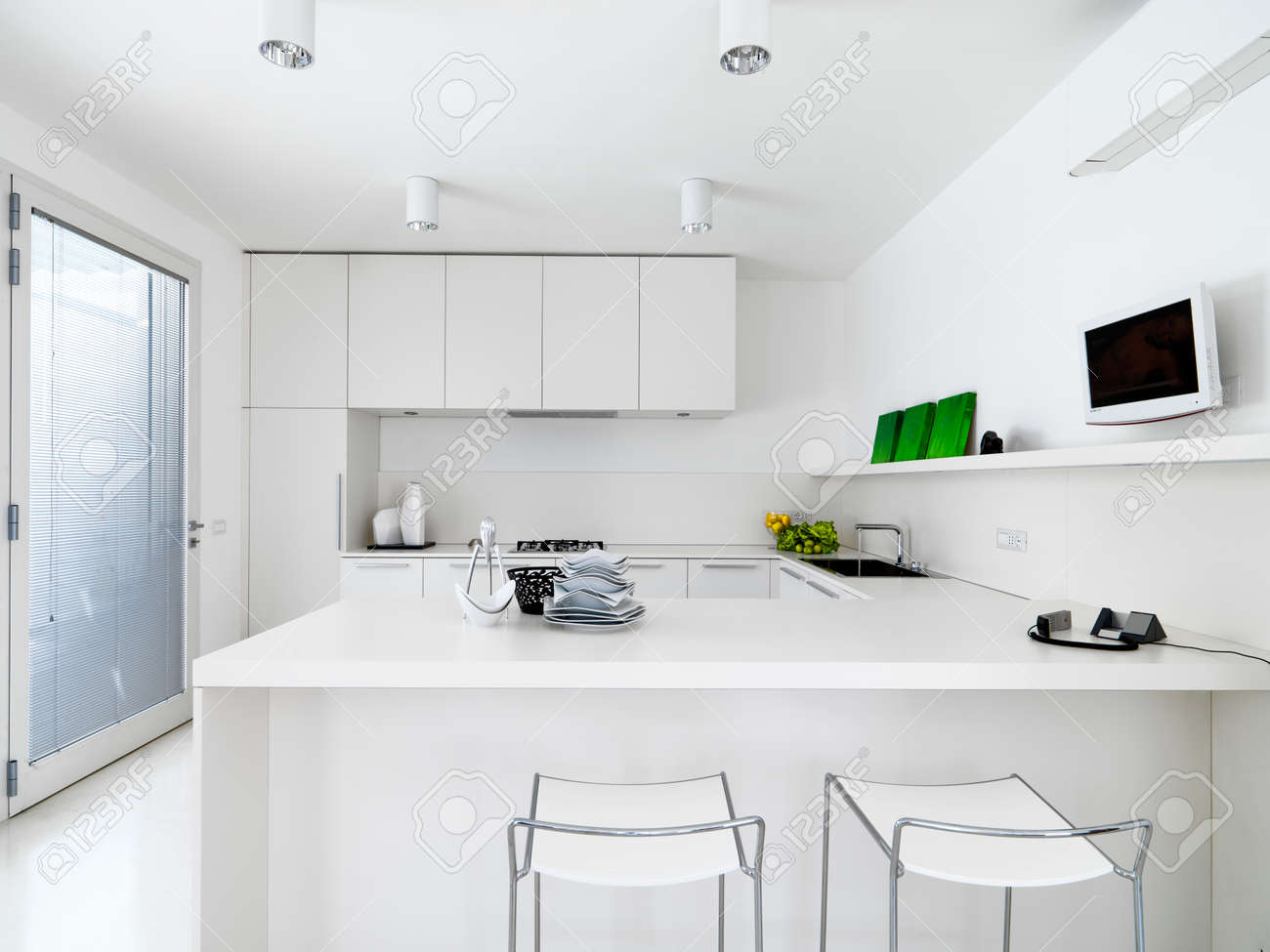 Interior View Of A White Modern Kitchen With Vegetables On The