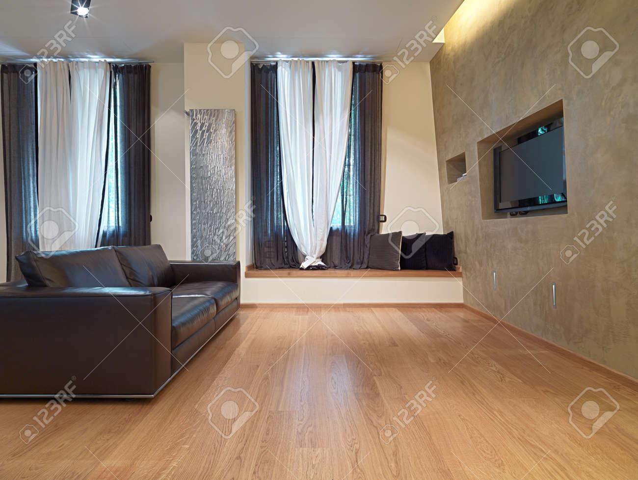 Canapé en cuir brun dans le salon moderne avec plancher de bois et ...