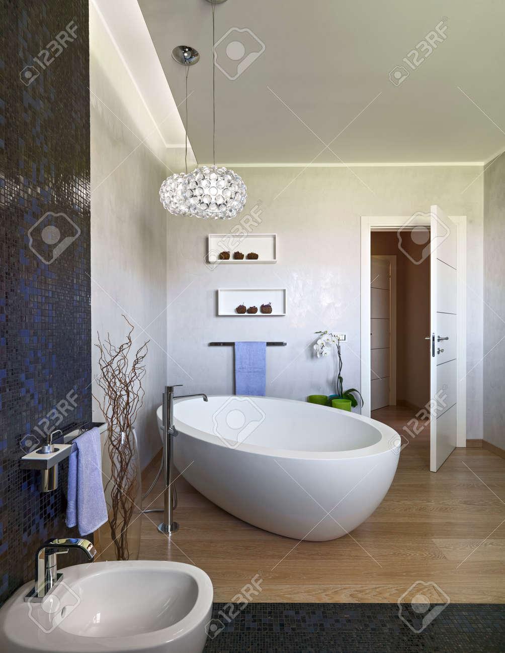 Foeground de una bañera en el cuarto de baño moderno wgich Foor es de madera