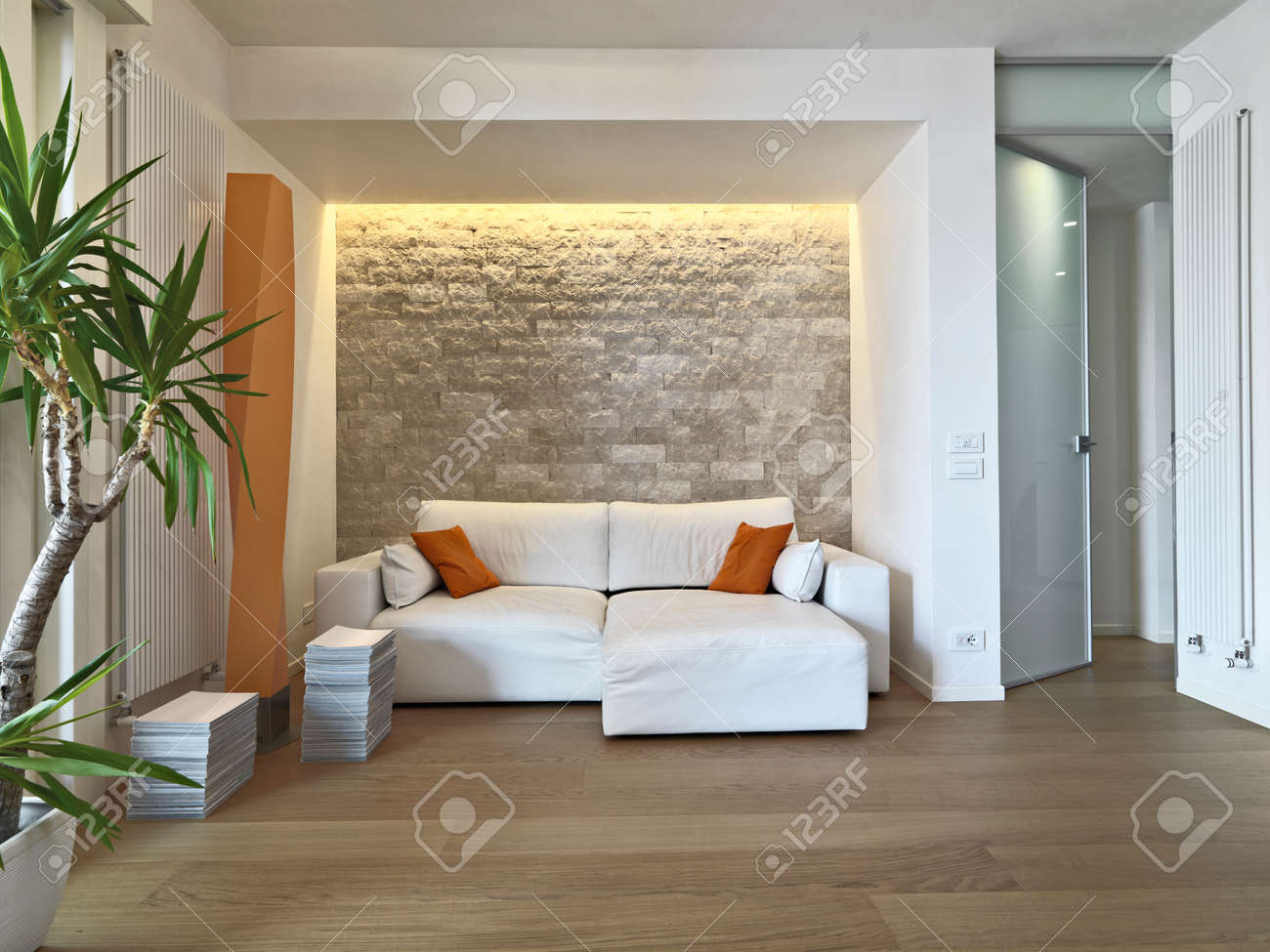 interior view of modern livig room in foreground the leather sofa with orange pillow and wood floor Standard-Bild - 49591539