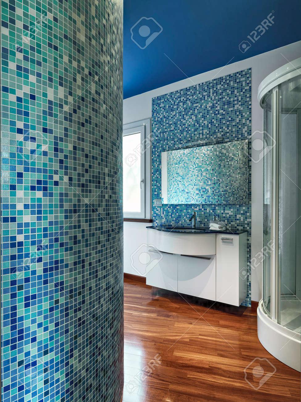 Ver iinterior de un moderno cuarto de baño con azulejos de mosaico, piso de  madera y techo pintado de azul