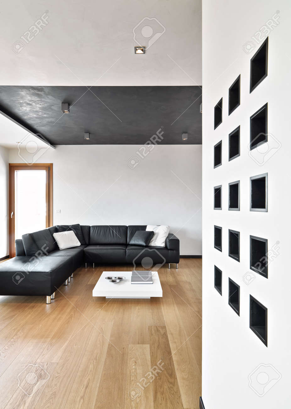 Canapé en cuir noir dans le salon moderne wit plancher de bois