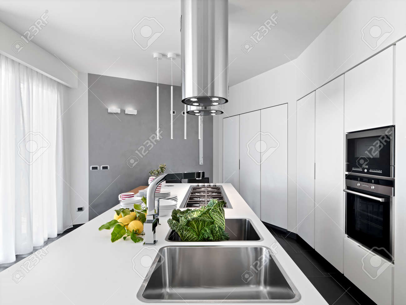 internal view of a modern kitchen in foreground still sink with vegetable and lemons on the worktop - 50767127