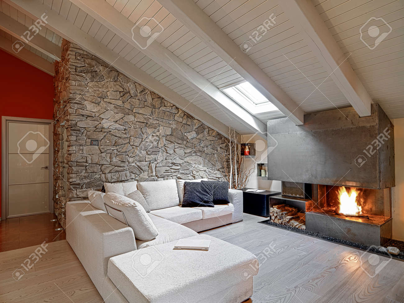Modern Living Room With Fireplace In The Attic And Wood Floor Stock Photo