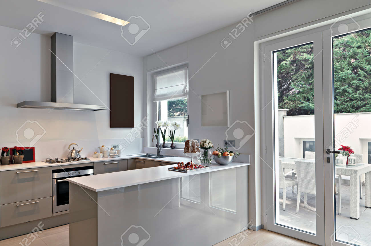 view of a modern kitchen with kitchen island overlooking on the terrace Standard-Bild - 56652759