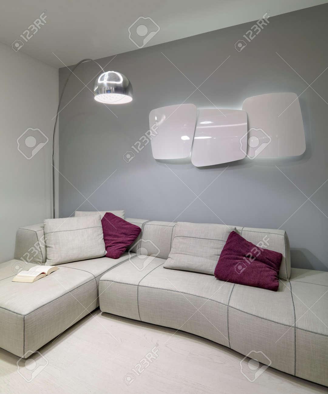 Détail de canapé en tissu avec oreiller violet dans le salon moderne avec  chauffage sur la lampe loor mur andf