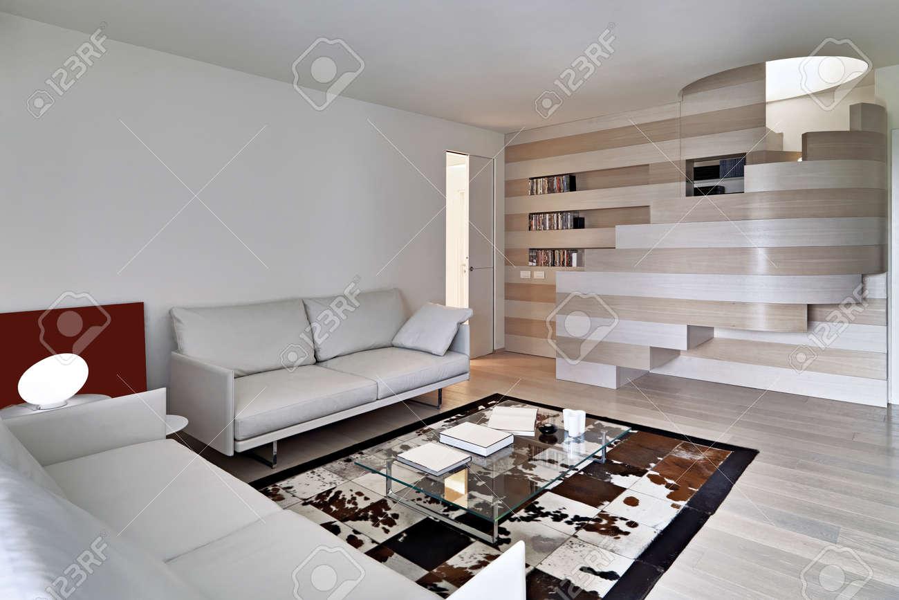Salon moderne au premier plan le canapé en cuir avec vue sur la grande  bibliothèque