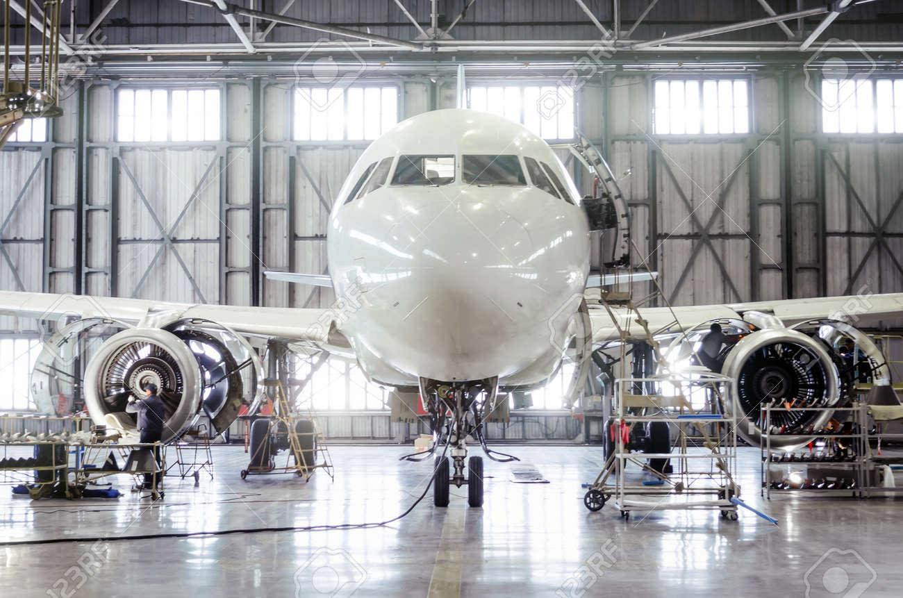 Passenger aircraft on maintenance of engine and fuselage repair in airport hangar - 91702440