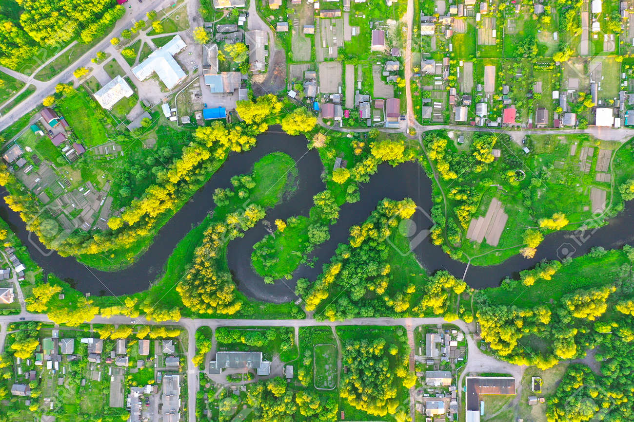 Aerial view landscape of winding small river among the small town, stream in green field - 124682019