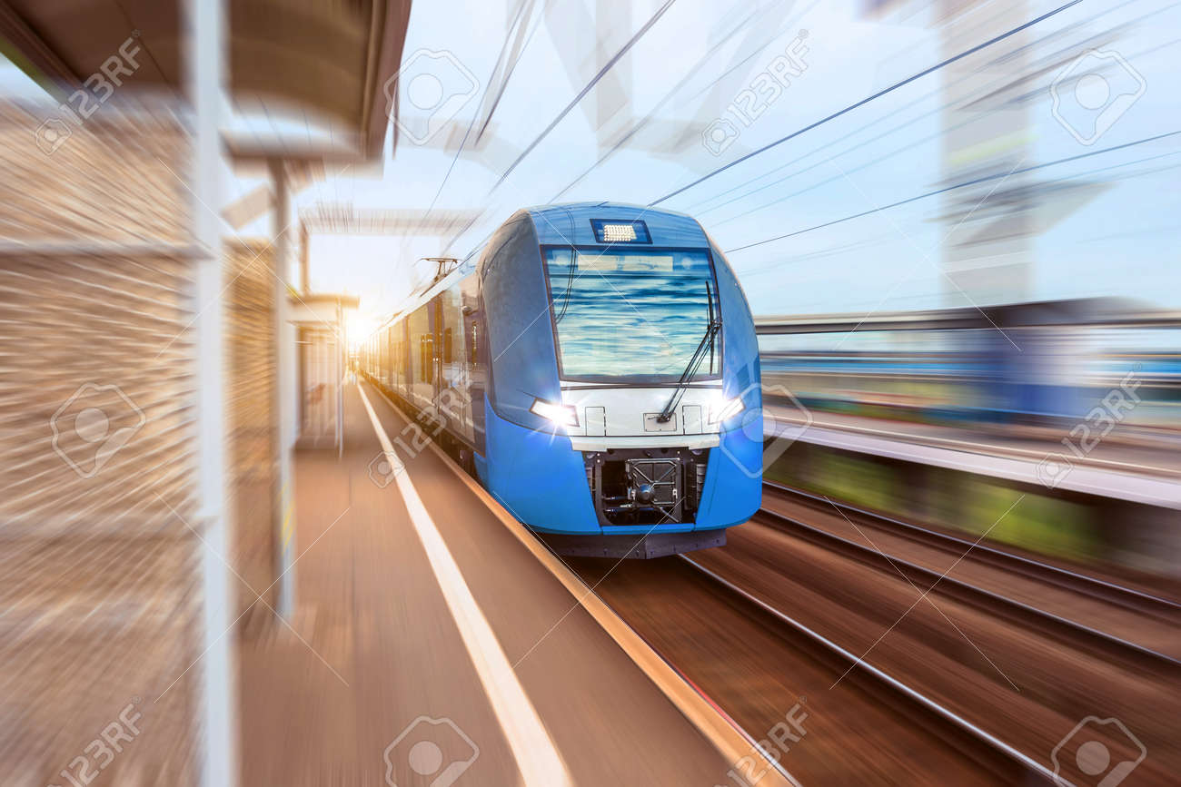 Electric train at high speed rides past the passenger platform station in the city - 129843828
