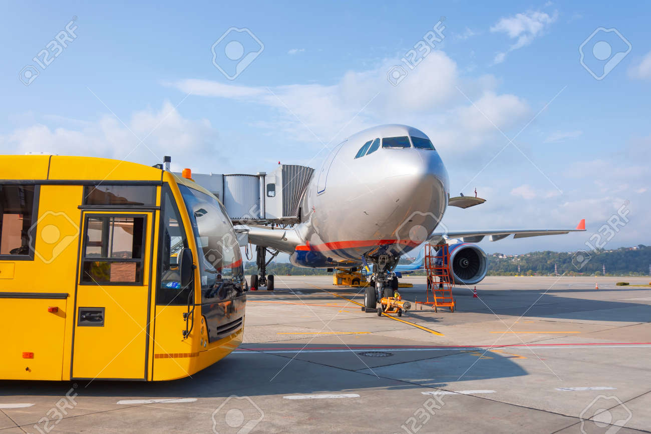 Shuttle yellow bus waiting for passengers on the plane for transportation to the airport terminal. Aircraft arrival background. Travel tourist destination concept - 135931854